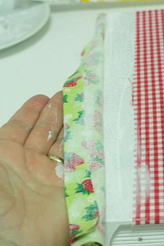 3- Faça uma dobra no tecido estampado e cole na lombada do livro. Passe um pouco por cima do tecido xadrez. Para abrir o livro, faça um pequeno pique com o estilete no tecido estampado, na parte de baixo e de cima da lombada.