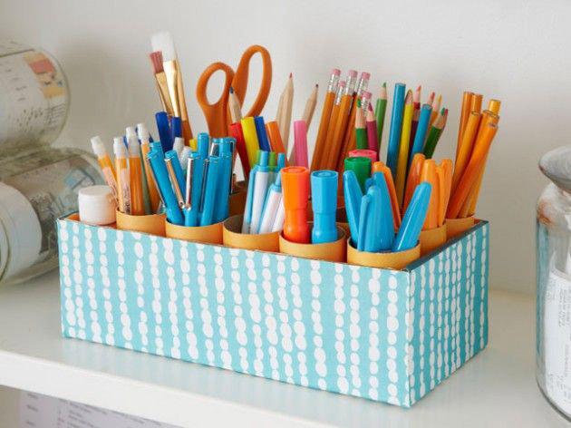 Rolos de papel higiênico acomodado em uma caixa forrada dão uma bela organizada nas canetas e nos lápis.